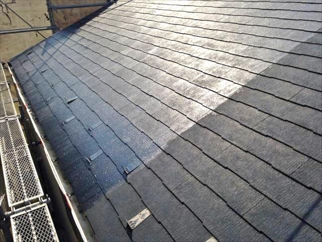 屋根塗装の下塗り中です。奥の光っている部分が下塗り済み。