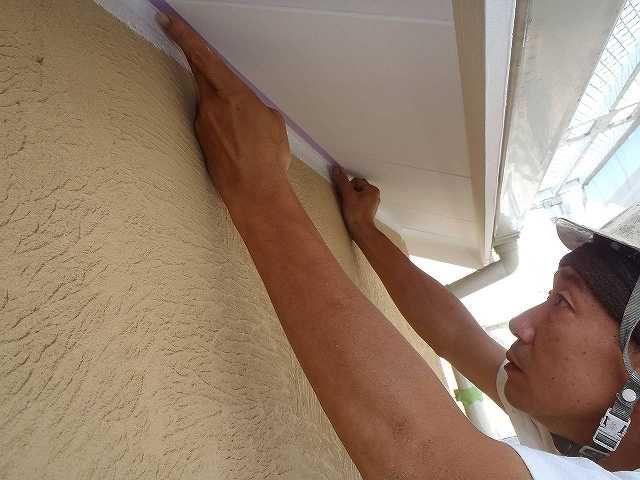 軒裏にマスキングテープを貼る塗装職人