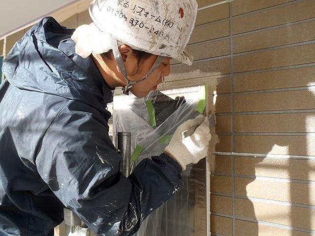サッシ廻りのテープとの境目のダメ込みを行う塗装職人
