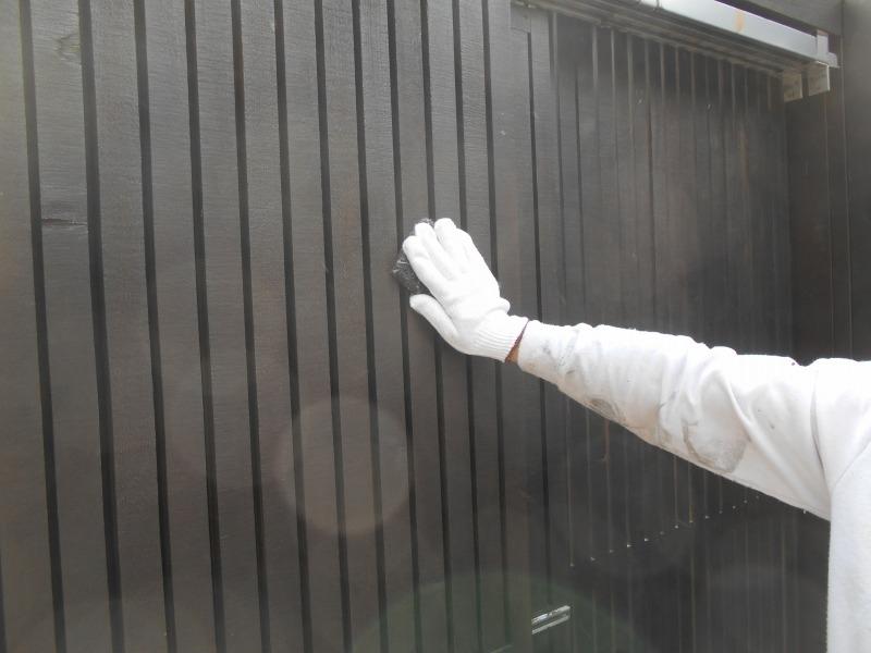 ウッドフェンスを塗装するため、表面を研磨しています。