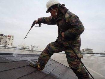 屋根の高圧洗浄をする職人