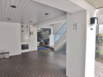 施工後の1階エントランス内。壁に加え、奥の手すり・鉄扉も綺麗になり、明るい空間を演出しています。