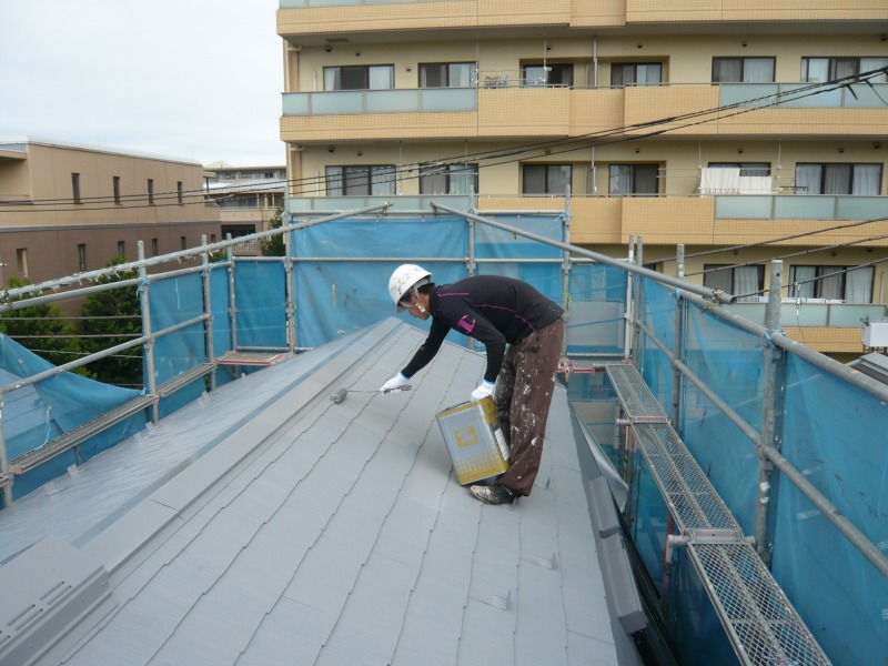 中塗りまで終わっている屋根を、塗料片手に上塗りをしています。