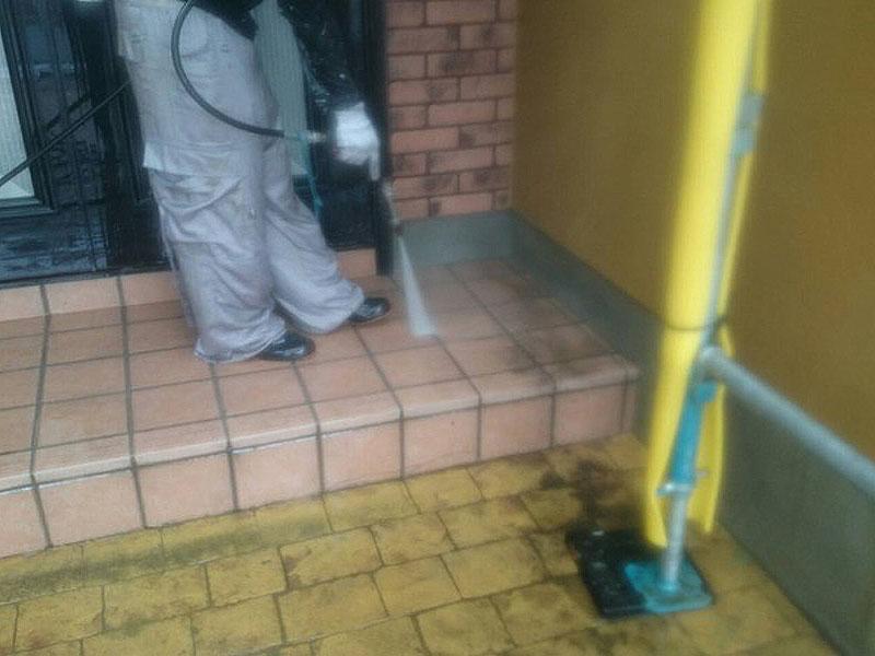 玄関のタイルを洗浄しています。細かい水しぶきが飛んでいます。