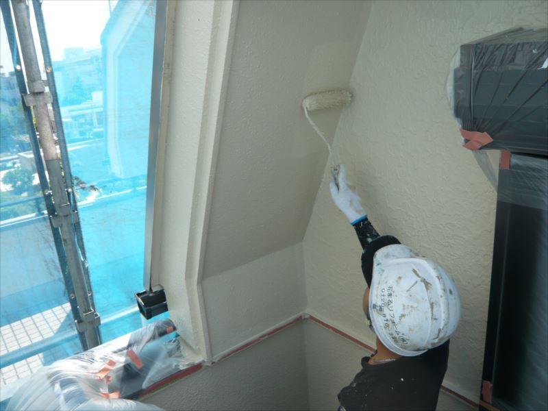 ローラーを使って、外壁の上塗りを行っています。