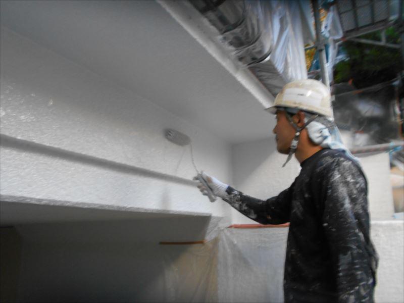 車庫の入口部分を塗っています。窓の桟等、塗らない場所は養生してあります。