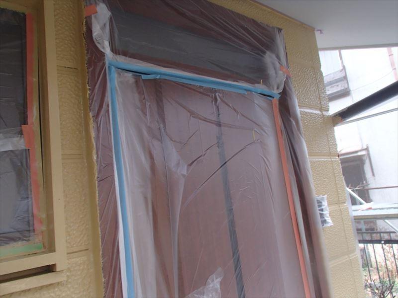 玄関周りの中塗り中。汚れないようにしっかりと養生しています。