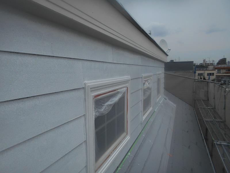 外壁の中塗りをしています。窓が汚れないようにしっかりと養生しています。