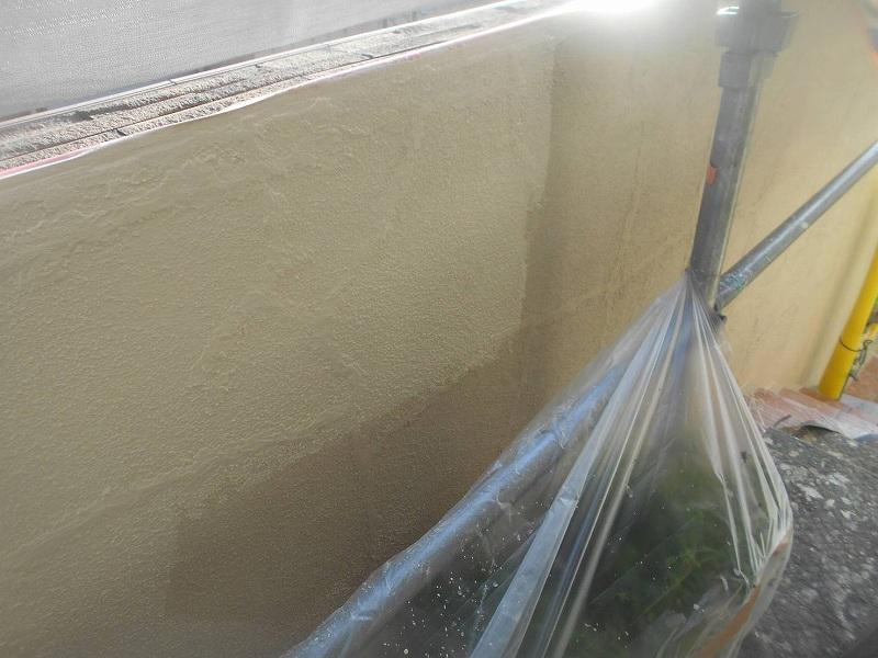 植木に養生をして塀を塗装しています。