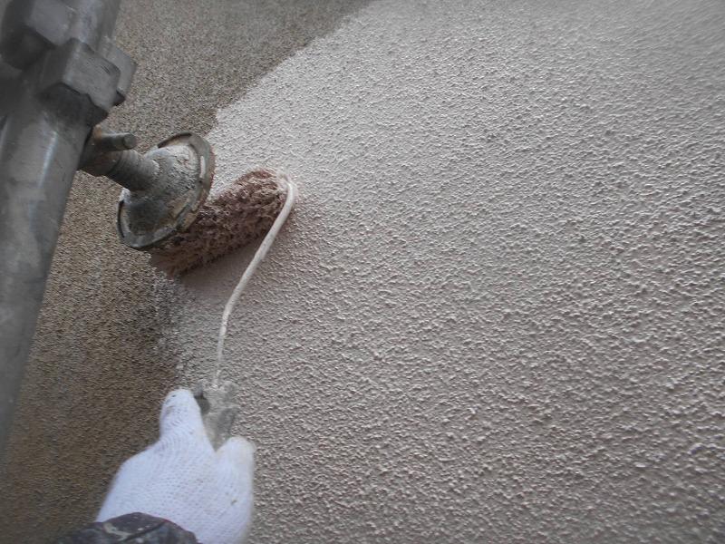 外壁の中塗りをしています。足場の揺れを抑える壁当ては、塗装する部分だけ浮かせて作業をしています。