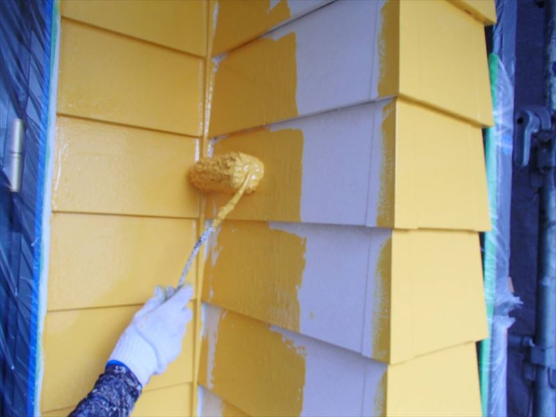 こちらは中塗り作業中。外壁の広い面積をローラーを使って塗っています。
