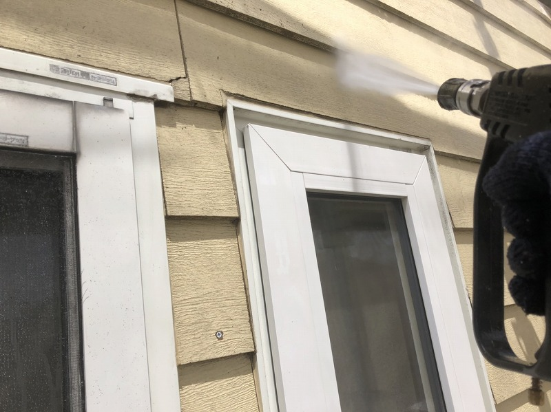 こちらも高圧洗浄の様子。外壁のひび割れは水圧が当たりすぎないように注意しています。