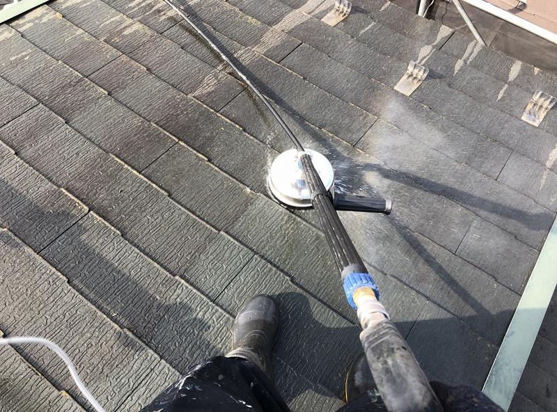 ブラシの付いたサーフェスクリーナーを使って屋根の汚れを高圧洗浄で落としています。