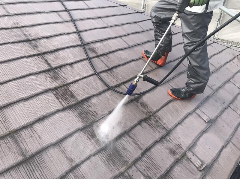 屋根の汚れを落とす高圧線市場は、長靴に雨合羽を着て作業を行います。