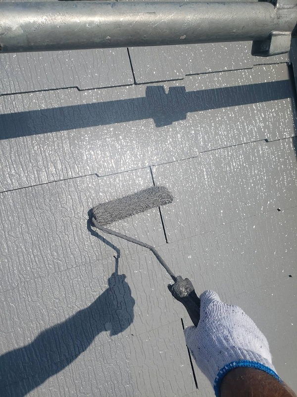 屋根のトップコート2回目。上塗りをした場所は、表面のキメが整い、光沢が出ています。