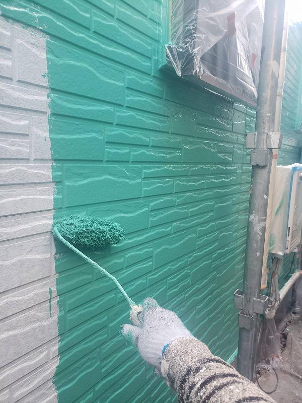 サイディングの壁の部分はトップコートの1回目として中塗りを行いました。塗料がついて困る場所はシートで覆って養生しています。