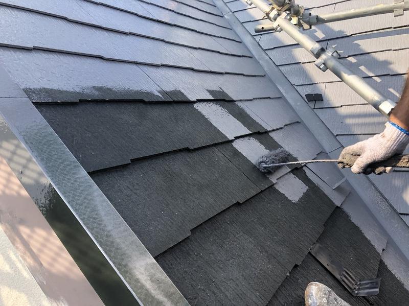 屋根のトップコートの1回目の塗装の様子。取付けてある雪止め金具も一緒に塗っていきます。