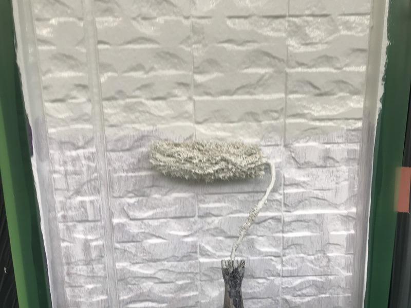 玄関と窓のサッシに塗料がつかないようにしっかりとシートで覆った上に、塗料が当たらないように養生テープを立てて羽根のように貼っています。