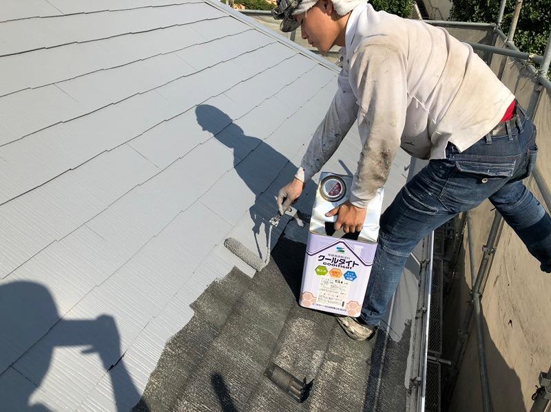 屋根の中塗りの様子です。塗料の缶のふたを細工して、缶を手元に持って塗っています。