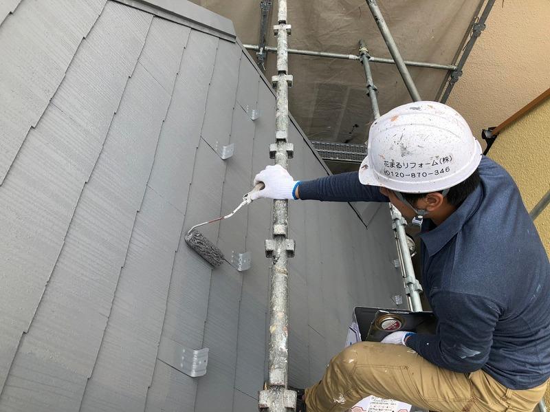 屋根の勾配がきついので、足場のパイプ部分で上手く体を支えながら作業しています。