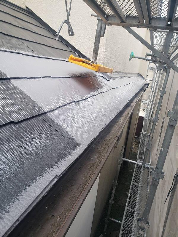 屋根の中塗りの様子。足場が屋根についている部分は一時的に足場を持ち上げて塗装します。