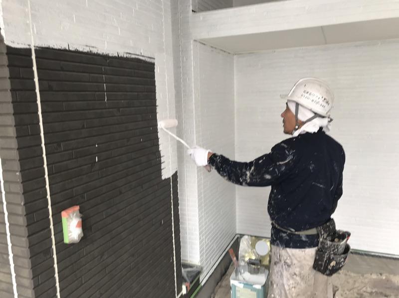 白い下塗り材を外壁に塗っています。