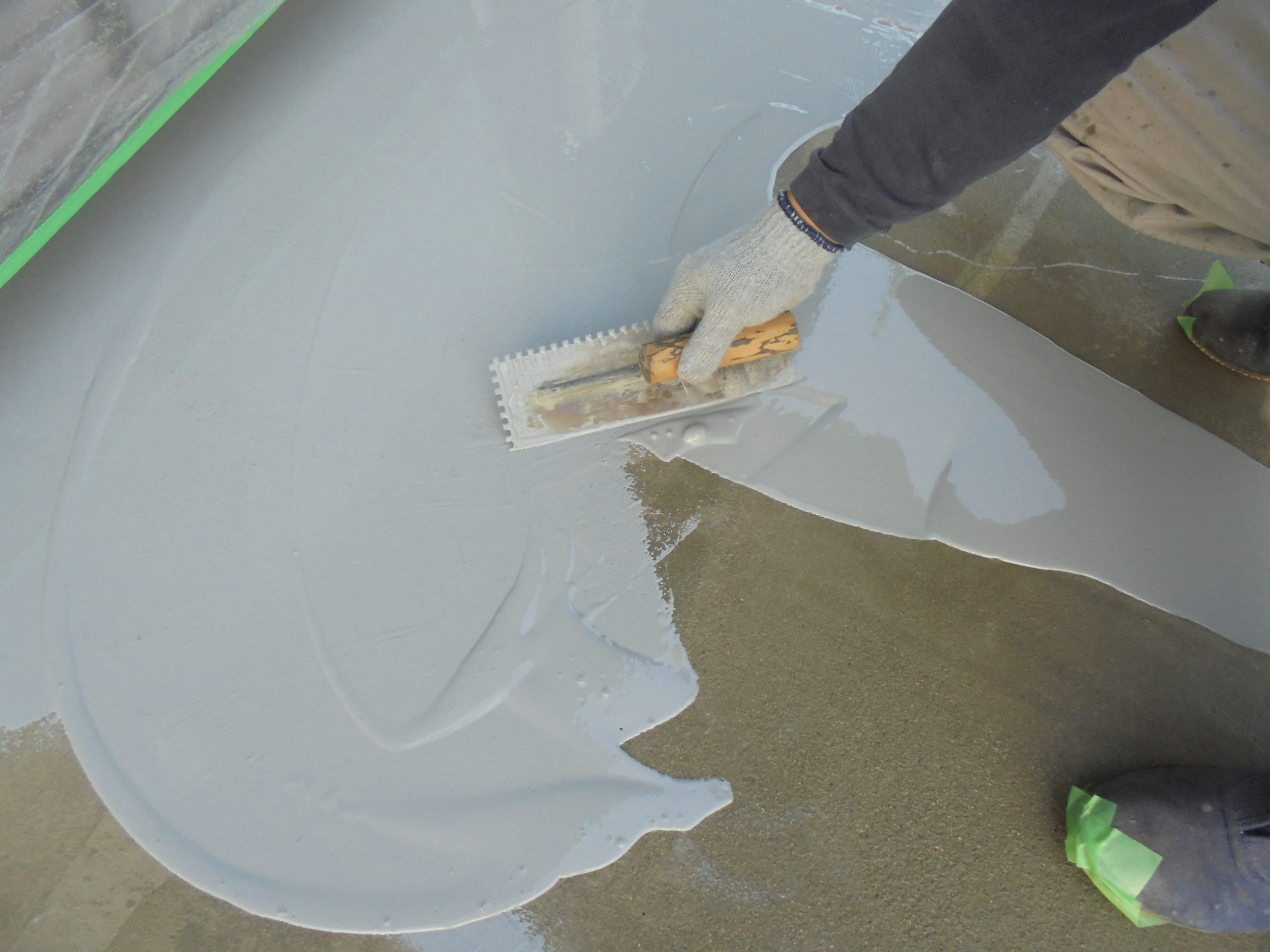 ベランダに下塗り材を塗った後、防水の塗料を丁寧に塗っていきます。