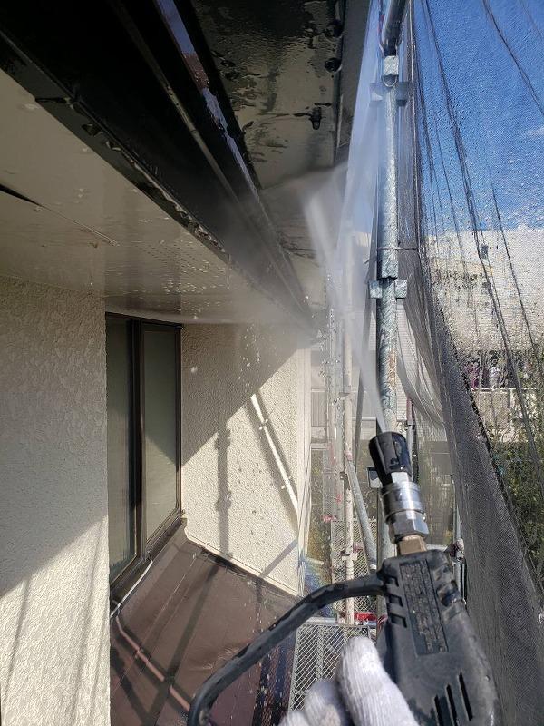 外壁の汚れを高圧洗浄で落としています。メッシュシートをかけているので、水の飛び散りは最小限で済みます。
