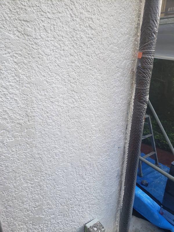 外壁の下塗りを行いました。雨樋に塗料が付かないように養生しています。