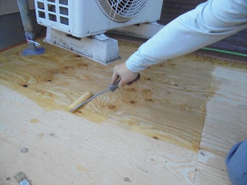 ベニヤの上に下塗り材を塗っていきます。エアコンの室外機は動かせないため、宙に吊って作業しています。