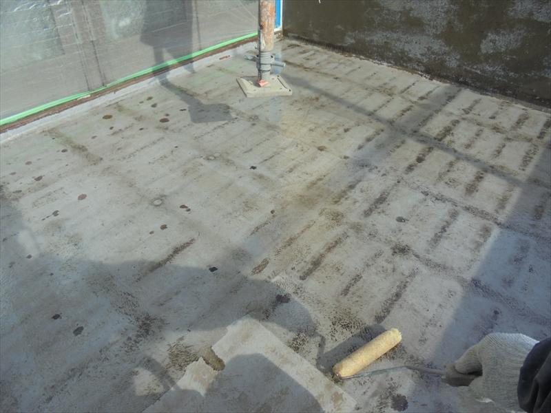 ベランダに防水用の下塗り材を丁寧に塗り込んでいます。