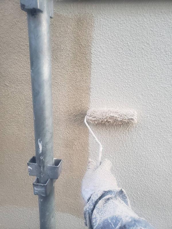 外壁の中塗りがスタートしました。下塗り材は白っぽい半透明の塗料なので、最初の壁の色が透けて見えます。なので、下塗りと中塗りの境目がよく分かります。
