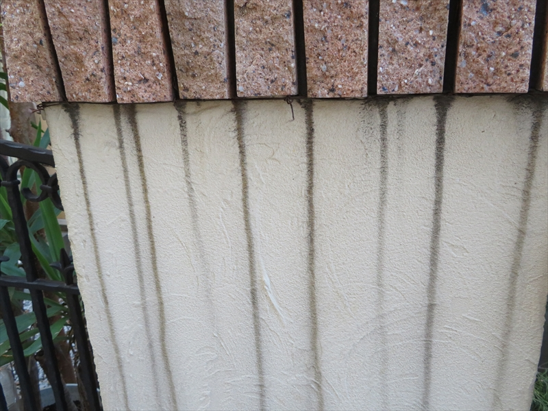 門柱の飾りタイルの溝から雨水が垂れて黒い線になっています。