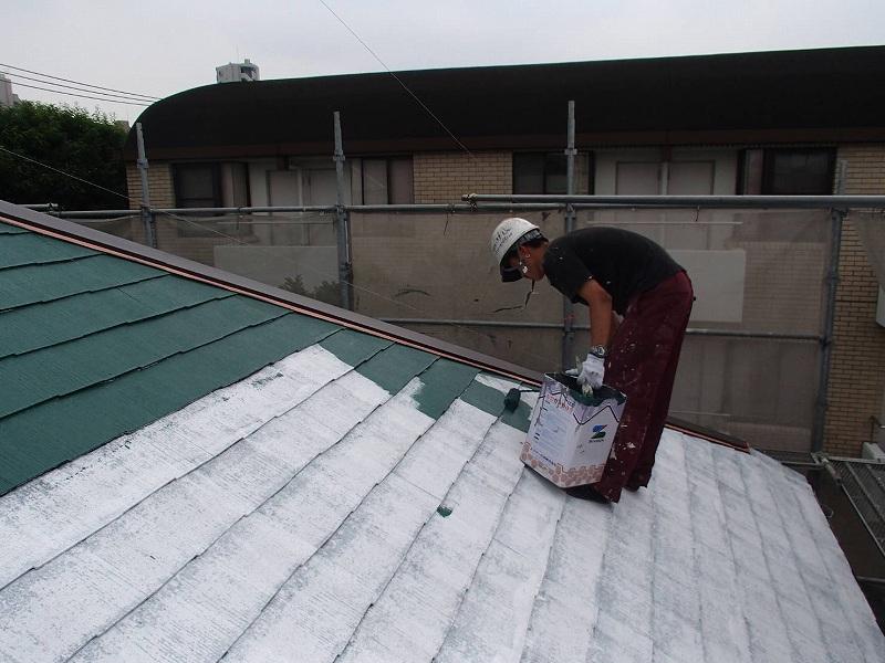 屋根の中塗りをしています。塗料の缶は持ちやすいように蓋の部分を加工して使っています。