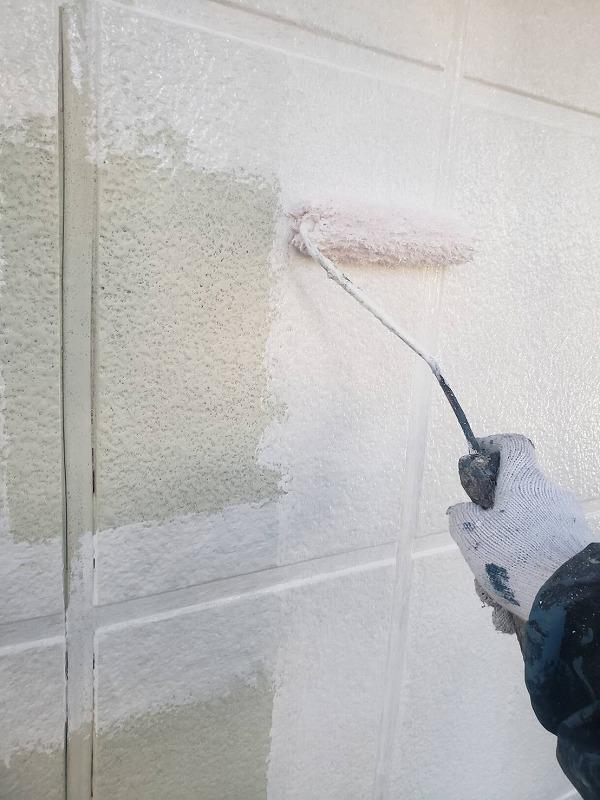 外壁の下塗り作業です。横の目地の凹凸部分に先に塗って、塗装漏れがないように注意しています。