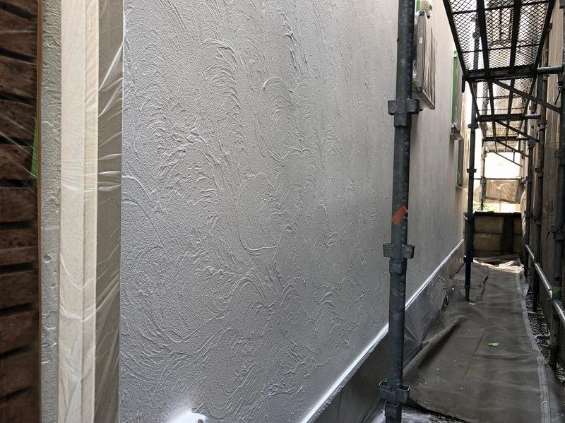 左側にあるタイルや雨樋等の配管類は、塗料が付くと困るのでしっかりと覆って塗装しています。