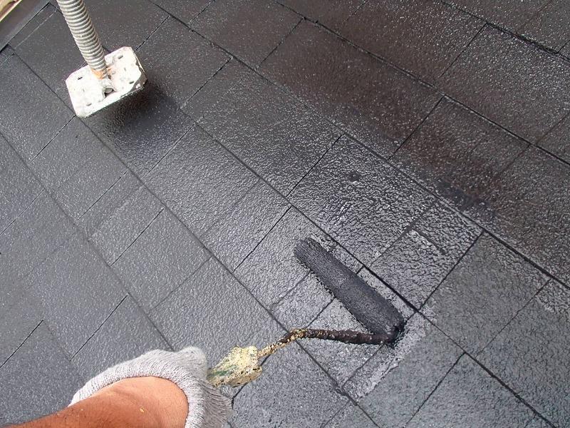 屋根の上塗り中です。屋根に足場がかかっている場合は、1本ずつバランスを見ながら上に上げて隙間を作り、塗装をしています。