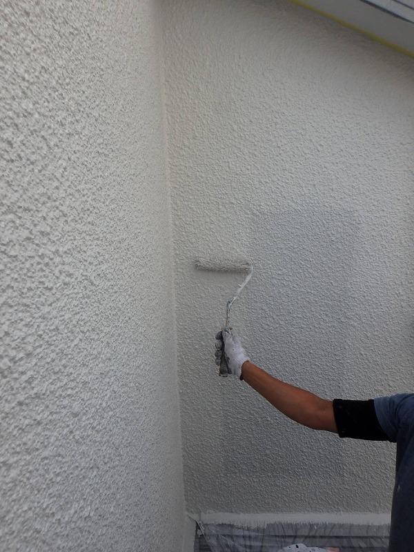 外壁のモルタル面の上塗りをしています。上下の凹凸が多い部分から塗り始めたため、ちょうど中央が最後に塗る場所になりました。