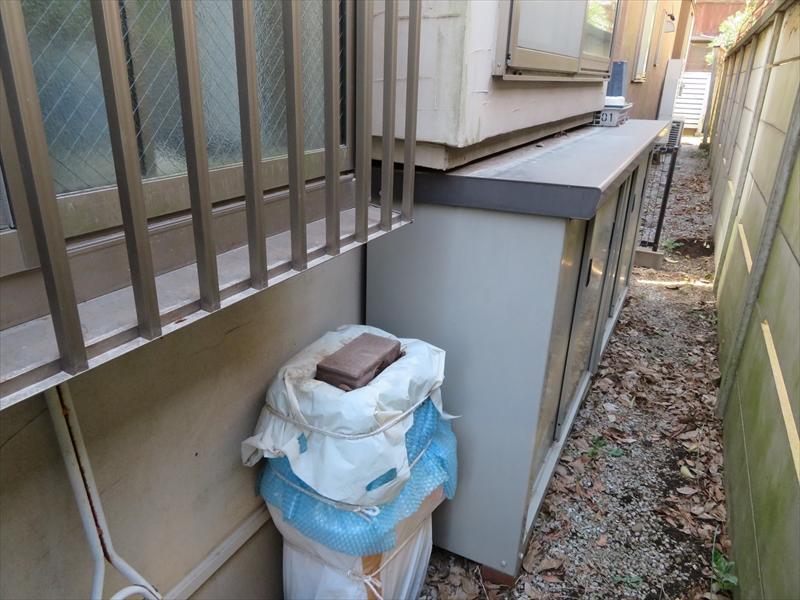 外壁にピッタリとつけられた物置。足場を立てた後は動かせるスペースがなくなるため、完全に移動させるか、この後ろの外壁は塗装しない(物置に覆われているので劣化は少ない)の2択になります。
