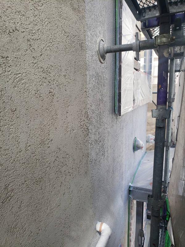 外壁の塗装中、足場の揺れを低減させる「壁当て」という金具を外壁から離して塗装しています。