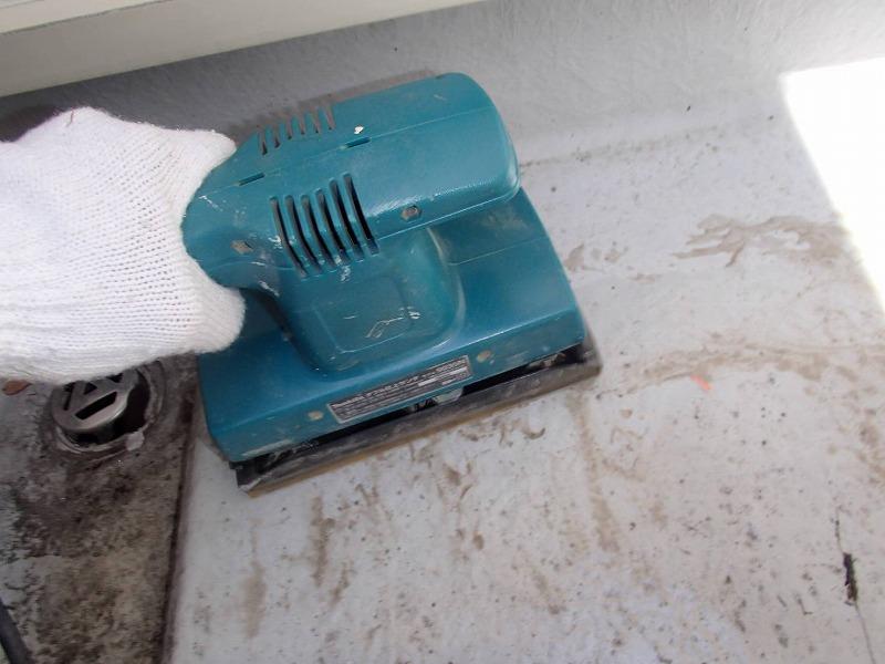 ベランダの防水トップコートの塗替えでは、前回の塗料を電動工具で削り落とします。