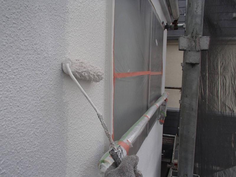 外壁の中塗りの様子。塗料がつかないように窓にシートをはって養生しています。