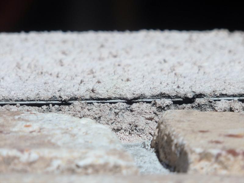 外壁のタイル部分とモルタル部分の境目で、モルタル部分が削れて、きれいな角を出すための金属の線が見えています。