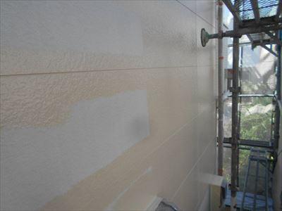 外壁の中塗り中。サイディングの境目のシールを丁寧に塗ってから、全体を塗っていきます。