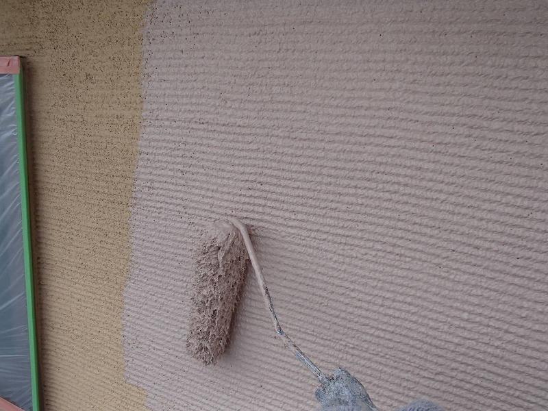 外壁の中塗りをしています。外壁の凹凸に合わせて、ローラーで塗る向きが決まります。