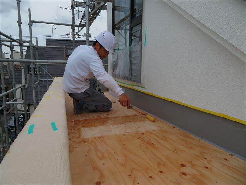 ベランダの防水工事をやり直すため、ベニヤ板を貼り直し、下地材を塗装しています。