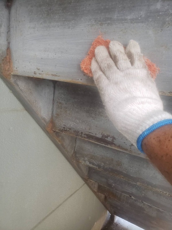 鉄部の階段の裏側のサビや汚れを金属製のスポンジで削り落としています。