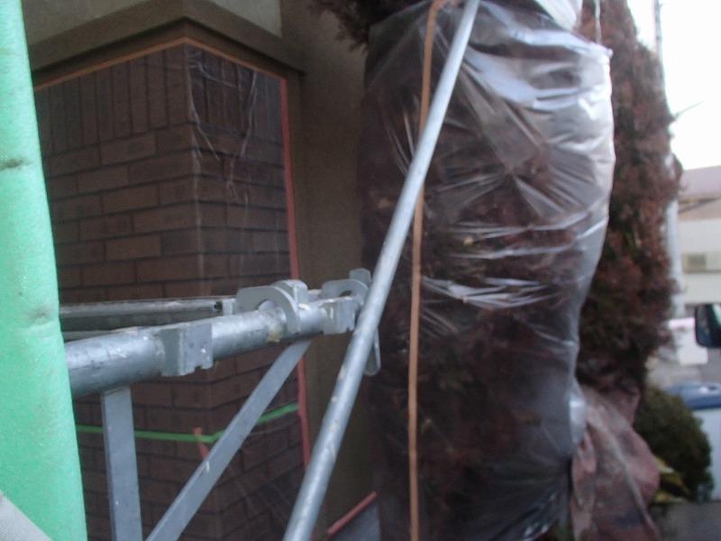 塗料がつかないように植栽やタイル面に養生しています。