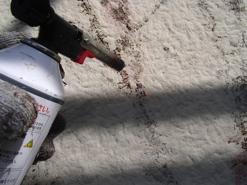 外壁に入り込んでしまっているツタを、バーナーで焼いて除去します。