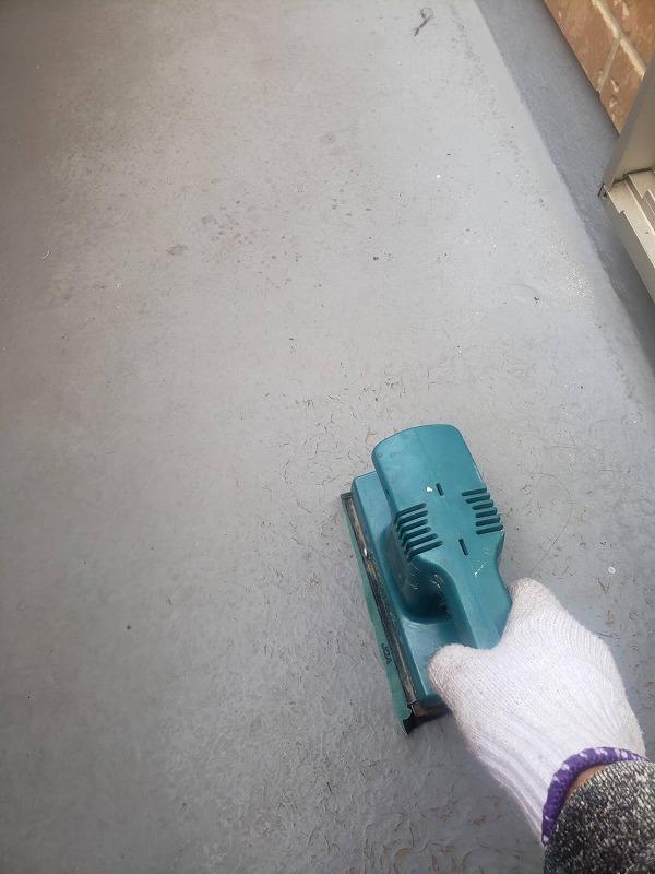 ベランダの防水塗料がよく付くように、前回の塗装を荒く削ります。